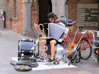 Straßenmusiker - Musikinstrumente, Konzertgitarre, E-Gitarre, Becken, kleine Trommel, große Trommel, Ventilposaune, Schellenkranz, Notenständer, Akkordeon, Schlagzeug, Blasinstrument, Saiteninstrument, Melone, Noten, Alleinunterhalter, Musiker, Straßenmusiker