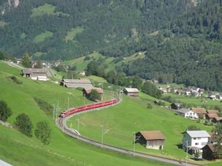 Eisenbahn- Schweiz - Schweiz, Bahn, Eisenbahn, Schienenverkehr, Personenverkehr, Zug, Schienenstrecke, Tal, Berg, Gebirge, Alpen, E-Lok, elektrifiziert, Strommasten, Wiese, Alm, Scheunen
