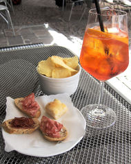 Aperol Spritz auf italienische Art - Aperol, Spritz, Likör, Italien, orange, bitter, Weißwein, Glas, Apéritiv, Getränk, trinken, Chips, Kartoffelchips, Snack, Imbiss