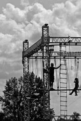 Klettern im Freien auf der mobilen Hochseilanlage - Hochseilgarten, Mut, mutig, helfen, Team, Teamsport, überwinden, über sich hinauswachsen, Ethik, neue Wege gehen, Angst, Wagnis, Seil, überqueren, Abgrund, Sport, Abenteuer, turnen, Freizeit, klettern, schwindelfrei, Freizeitsport