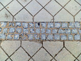 Ausschnitt einer Gehwegpflasterung - Pflaster, Pflasterstein, Struktur, Muster, Stein, Hintergrund, Wallpaper, Layout, Boden, versetzt, Fuge, Linie, Material, Nahaufnahme, Oberfläche, angeordnet, ausgerichtet, Wegstrecke