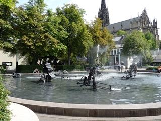 der Fastnachtsbrunnen – Basel # 2 - Jean Tinguely, Basel, Fastnachtsbrunnen, Kunst, Künstler, Plastik, Skulptur, Wasserfontäne, Wasserspiel, Wasserbecken, Maschinenskulpturen, Bäume, Kirche