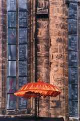Bunter Schirm vor Kirchmauer - Schirm, farbenfroh, bunt, Kirchenmauer, Kirche, Kontrast, Schreibanlass, orange, rosa