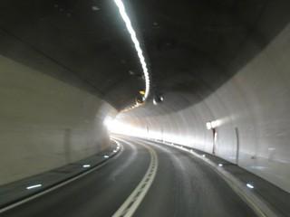 Tunnel - Tunnel, Straßentunnel, Tunnelröhre, Röhre, Beleuchtung, Licht, Licht am Ende des Tunnels, Ventilator, Luftversorgung, durchgezogene Linie, Überholverbot, Fluchtweg, Fluchtwegtür, Asphalt, Alpen, Schweiz, Beton, Betonwand, Kurve