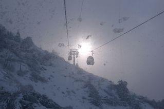 Gondeln im Gegenlicht - Gondeln, Seilbahn, Schnee, Schneetreiben, Schneegestöber, Schneesturm, Gegenlicht, Licht, Hochgebirge, Hang, Einsamkeit, Winter, eisig, kalt, trüb