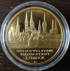Gold - Holstentor, Trave, Marienkirche, Gold, Goldmünze, Au, Aurum, Petrikirche, Edelmetall, Feingold, Unze, Feinunze, Unesco, Welterbe, Lübeck, Skyline, Stadtpanorama, Panorama, Hanse, Hansestadt, Münze, Geldanlage