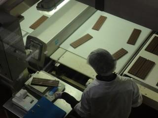 Schokoladenfabrik1 - Schokolade, Genussmittel, Milchprodukt, Kakaoerzeugnis, Milch, Kakao, Schokoladenfabrik, Schweiz, Waage, Lebensmittelkontrolle, Kontrolle, Stichprobe, Fließband, Hygiene, Haarschutz, wiegen, Verpackung, Förderband