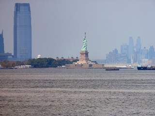 Freiheitsstatue mit Skyline von Manhattan - Manhattan, Statue of Liberty, Lady Liberty, Miss Liberty, Freiheitsstatue, neoklassizistisch, Statue, Kolossalstatue, Wahrzeichen, Freiheit, Symbol, auswandern, Sehenswürdigkeit, sight, New York, NY, NYC, Liberty Island, New Yorker Hafen, harbour, Weltkulturerbe