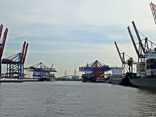 Containerhafen in Hamburg - Freie Hansestadt, Hamburg, Hafen, Warenumschlag, beladen, entladen, Fracht, Frachtgut, Elbe, Köhlbrandbrücke, Containerschiff, Schiff, Brücke, Stadt, Container, Containerbrücken, Welthandel, Import, Export, Hafenbecken, Kai, Kaimauer