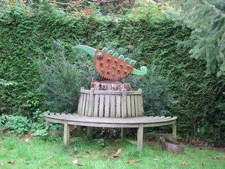 Café Winuwuk Bad Harzburg # 7 halbrunde Bank mit Skulptur - Bank, halbrund, Holz, Sitzmöbel, sitzen, ruhen, ausruhen, rasten, Meditation, Skulptur, Figur