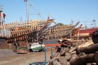 Schiffswerft auf Zypern_4 - Werft, Schiffswerft, Bootsbau, Bug, Holzschiff, Holzboot, Boot, Schiff, Schiffbau, Chaos, Zypern, Hafen, Planken, Holz, Durcheinander, Bootsskelett, Skelett, Gerüst, Rettungsboot, Mast, Holzstapel, Leiter