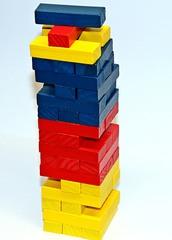 Matheturm vs. Wackelturm #2 - Matheturm, Wackelturm, Turm, Steinchen, Stein, Steine, Würfel, Quader, farbig, Mathematik, rechnen, stapeln, spielen, Spiel, zählen, werfen, Spiele, Zahl, Zahlen, rot, blau, gelb, Wahrscheinlichkeit, Körper, geometrisch, Seiten, Kanten, Ecken, Quadrate, Zufall, Illustration, rechnen, bauen, Holz, Oberfläche, Volumen, fünfzehn, Jenga