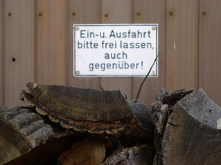 Garagentor mit Hinweisschild #2 - Garagentor, Einfahrt, Ausfahrt, Hinweis, Hinweisschild, Holz, Holzstapel, Schreibanlass