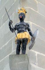 Mohr an einem Haus - Hinweis, Werbung, Zeichen, Mohr, Neger, Skulptur, Figur, schwarz, gold, alt, Kämpfer, Schild, Speer, Kopfschmuck